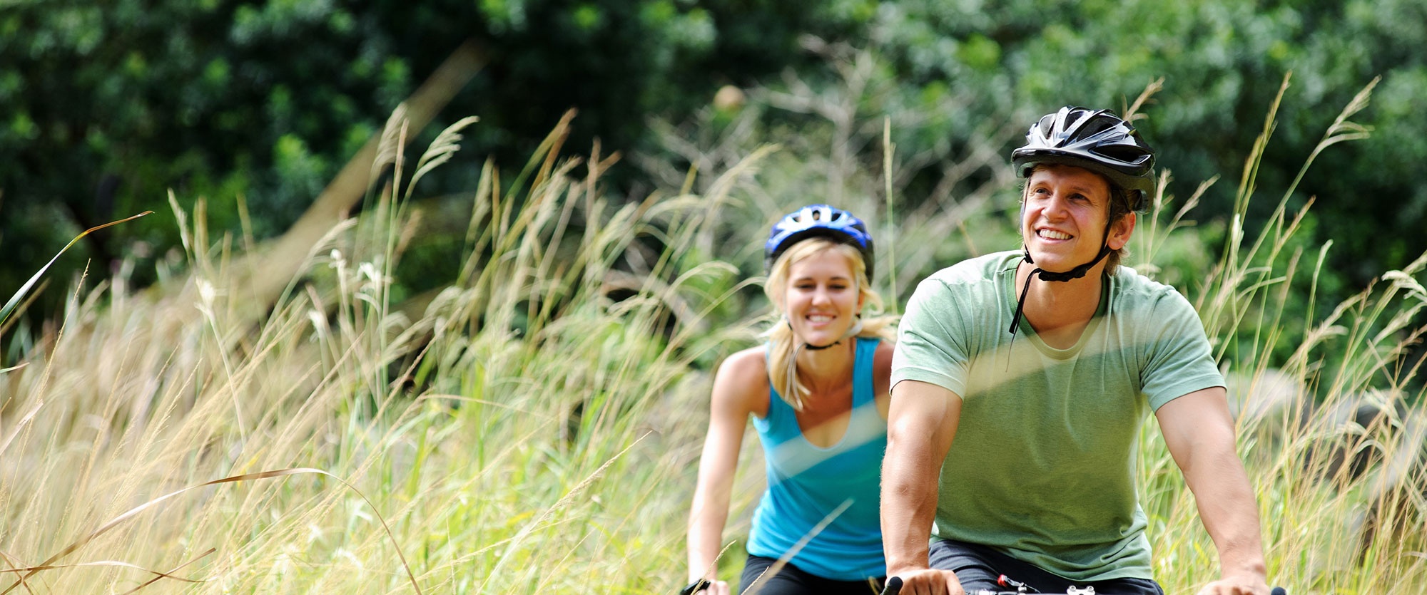 Man and woman biking through tall grass